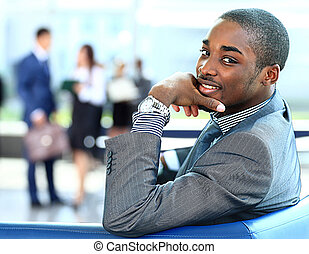 African American business man with executives working in background