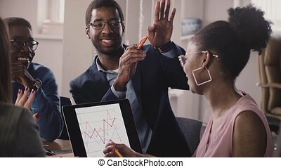 African American business people talk, show gestures and communicate at office meeting, looking at laptop diagrams. Happy start-up partners smile, discuss market currency chart on tablet screen.