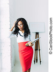 African-American business woman or teacher in glasses holding books and documents, standing on white background near big window