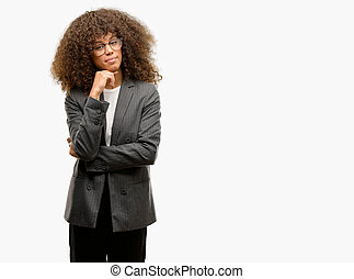 African american business woman wearing glasses with hand on chin thinking about question, pensive expression. Smiling with thoughtful face. Doubt concept.