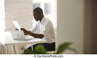 African american businessman consulting client, showing document with financial statistics