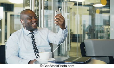 African American businessman in formal clothes smiling and talking to his family through smartphone webcam in a modern cafe. He waving his hand happily.