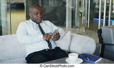 African American businessman in formal clothes typing sms on his smartphone in modern cafe during lunch break. He looks at screen and smiles happily