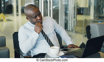 African American businessman in formal wear looking at his laptop and thinking over his business plan in stylish cafe during lunch break. He is thoughtful and thinking about project