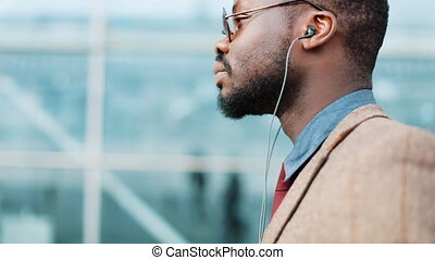 African American businessman listens to the music and dances while he walks near the office building with a smartphone. Concept: office worker, rest, advertising