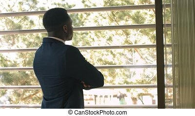 African-American businessman looking out of window with...