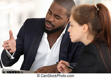 African american businessman mentor teaching caucasian intern with computer