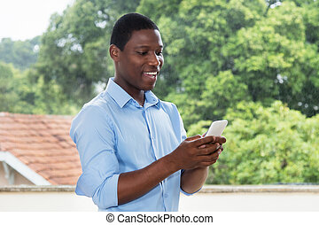 African american businessman sending text message with smartphone