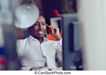 African American businessman sitting at the computer in startup office