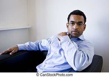 African American businessman sitting in armchair