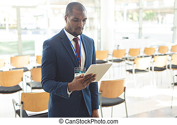 African-american businessman standing in conference room watching tablet