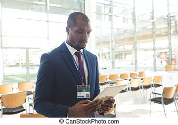 African-american businessman standing in conference room with tablet