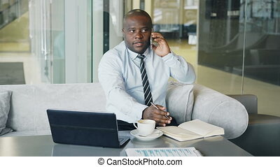 African American businessman talking on smartphone and writing down business information in his notepad sitting in glassy cafe with laptop and coffee on his table.