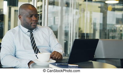 African American businessman thinking, printing and working on his laptop in glassy cafe during lunch break. He is brainstorming breakthrough ideas.