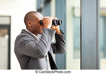 african american businessman using binoculars in office