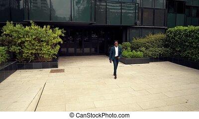 African American businessman wearing blue suit walking -...