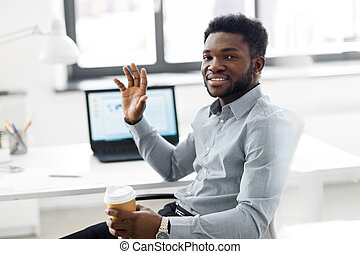 african american businessman with coffee at office