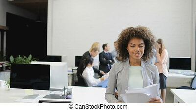 African American Businesswoman Analyzing Business Plan While Brainstorming Group Of Businesspeople Creating New Startup During Meeting In Modern Office