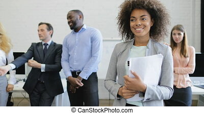 African American Businesswoman Hold Documents Smiling Over Business People Group Brainstorming Meeting In Modern Open Office