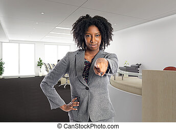 African American Businesswoman in an Office Pointing Forward...