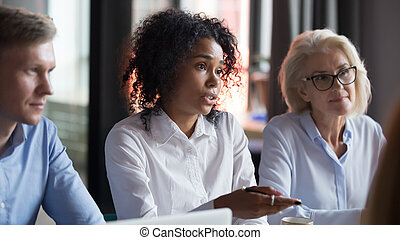 African American businesswoman talking with business partners at meeting