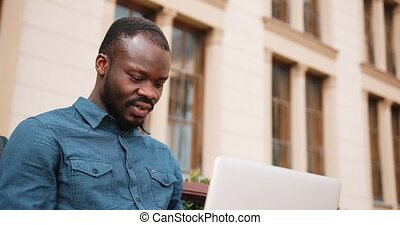 African American bussinesman sits on the bench and works on his laptop. Businessman working on his laptop in the park