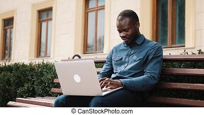 African American bussinesman sits on the bench and works on his laptop