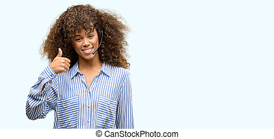 African american call center operator woman happy with big smile doing ok sign, thumb up with fingers, excellent sign