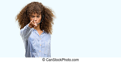 African american call center operator woman pointing with finger to the camera and to you, hand sign, positive and confident gesture from the front