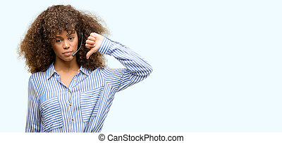 African american call center operator woman with angry face, negative sign showing dislike with thumbs down, rejection concept
