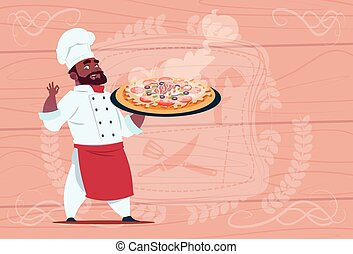 African American Chef Cook Holding Pizza Smiling Cartoon Chief In White Restaurant Uniform Over Wooden Textured Background