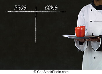 african american chef holding healthy food with chalk pros and cons on blackboard background