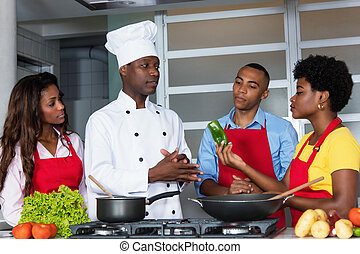 African american chef with women and man at kitchen