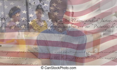 Animation of U.S. flag waving with U.S. Constitution text rolling over mixed race boy smiling with his family in the background. United States of America flag and holiday concept digital composition