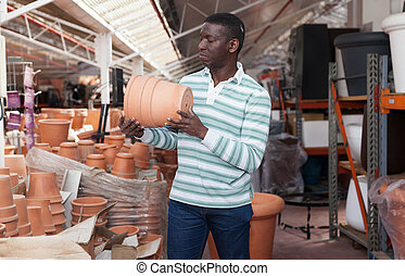 African American choosing pots for plants - African American...