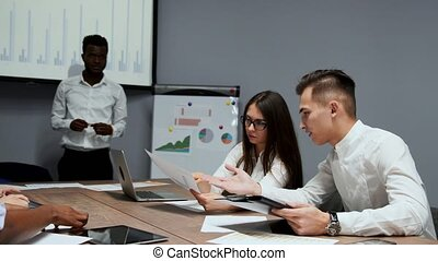 African american coach gives corporate presentation for businesspeople in office, dark skinned businessman presents new business plan on whiteboard, speaking to clients listening speaker at meeting