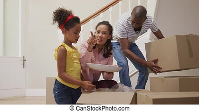 African American couple and their daughter moving into new house