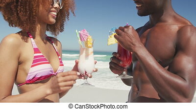 African american couple drinking cocktail seaside - Close up...