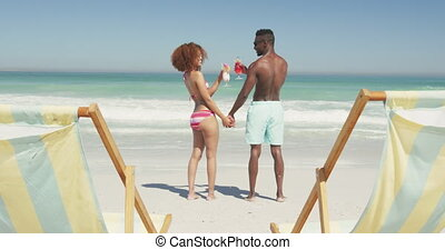 African american couple drinking cocktail seaside - Rear ...