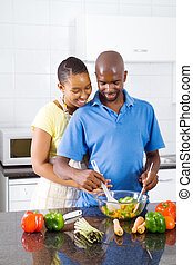 couple in kitchen making salad