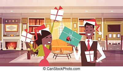 African American Couple In Santa Hats Holding Present Boxes In Living Room, Merry Christmas And Happy New Year Celebration Banner