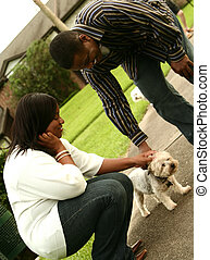 African American Couple Petting A Dog
