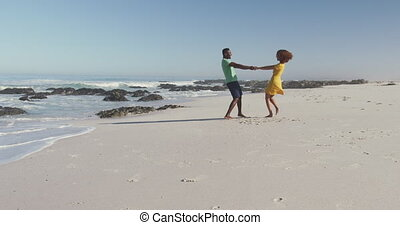 Front view distant of an African American couple enjoying time in the sun on a tropical beach, holding hands and turning, in slow motion