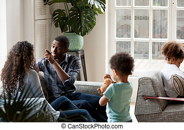 African American couple quarrelling at home on couch