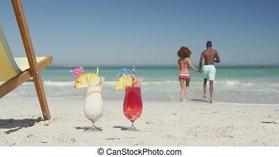 African american couple ready to swim with cocktail in ...