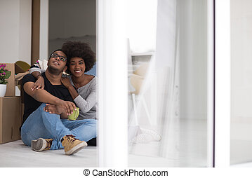 African American couple relaxing in new house