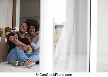 African American couple relaxing in new house - Relaxing in...