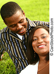 African American Couple Relaxing On The Grass