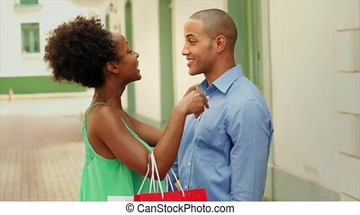 Black tourist heterosexual couple in Casco Antiguo - Panama City with shopping bags. The girl hold a credit card and kisses her boyfriend