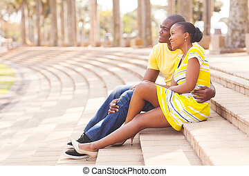african american couple sitting in park